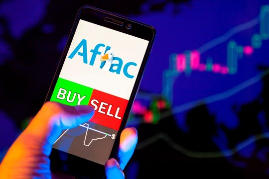 Company logo AFLAC Inc on smartphone screen, hand of trader holding mobile phone showing BUY or SELL on background of stock chart. Russia, Stavropol - May 29, 2019