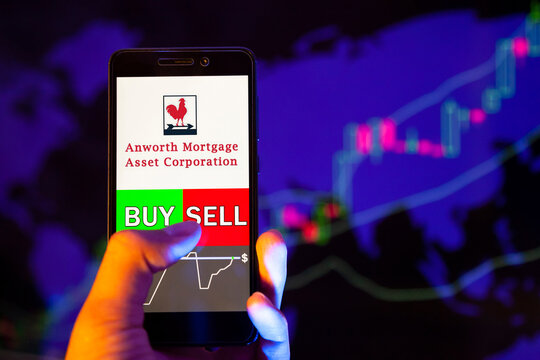 Company logo ANWORTH MORTGAGE ASSET CORP (ANH) on smartphone screen, hand of trader holding mobile phone showing BUY or SELL on background of stock chart. Russia, Stavropol, - May 25, 2019