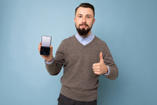 Closeup photo of amazing guy holding modern telephone hands casual outfit isolated on bright blue background