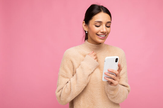 Young woman over isolated pink background sending a message with the mobile