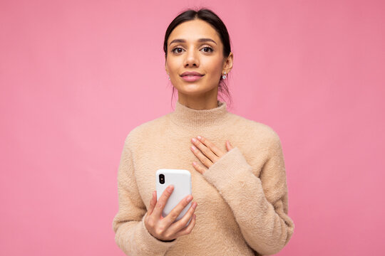 portrait of a gentle brunette on a pink background. holding a phone, looking at the camera