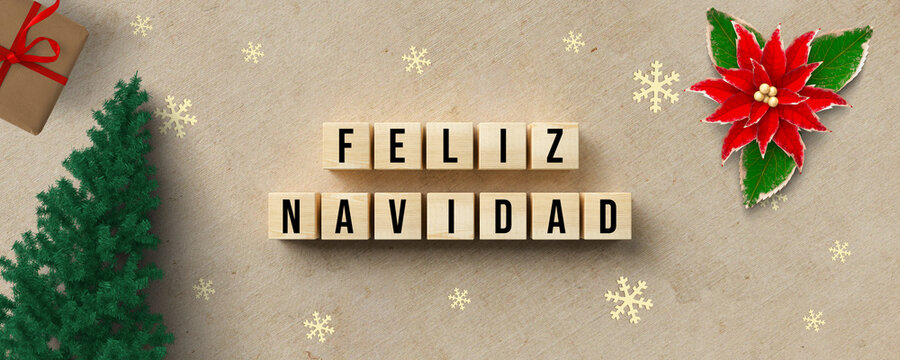 cubes with Spanish message for MERRY CHRISTMAS and christmas decoration on paper background