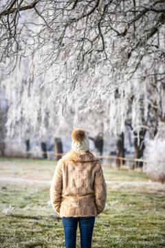 Woman wearing fake fur coat and enjoying walk outdoors in winter park