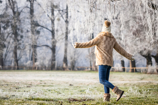 Happy woman enjoying winter nature with frozen trees