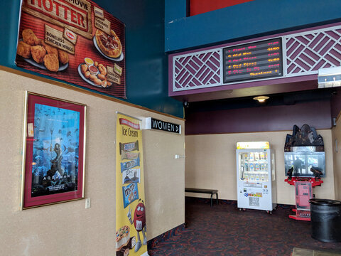 Kona, Hawaii - October 19, 2018: Inside Regal Cinemas Makalapua 10 with Aquaman Movie Poster, Ice Cream Ad, and Arcade Games in Hallway.