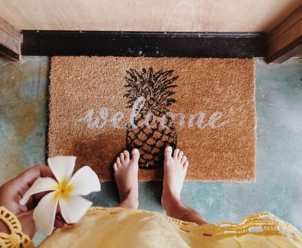 Low Section Of Woman Holding Frangipani By Welcome Sign Doormat