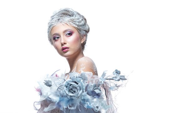 Winter Beauty Woman in clothes made of frozen flowers covered with frost, with snow on her face and shoulders. Christmas Girl Makeup. Make-up the snow Queen. Isolated on a white background.