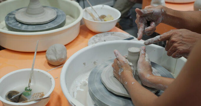 Hand work on pottery wheel, shaping a clay pot