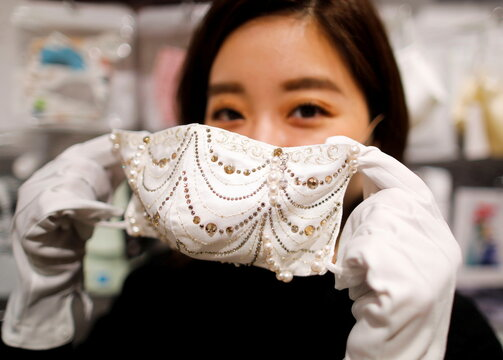 An employee of Cox Co, the operation company of the face-mask speciality shop Mask.com, shows off a luxury face mask decorated with the diamond, platinum and Swarovski crystals in Tokyo