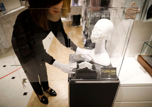 An employee of Cox Co, the operation company of the face-mask speciality shop Mask.com displays luxury face masks decorated with jewels or pearls in Tokyo