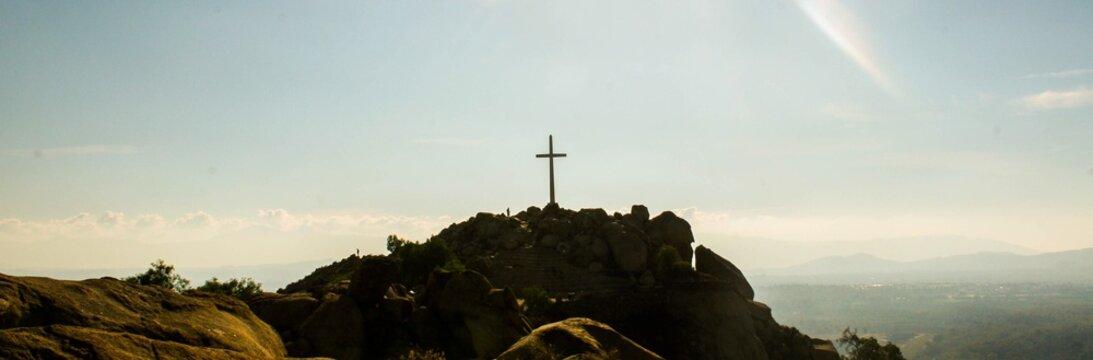 Cross On Mountain Peak Against Sky