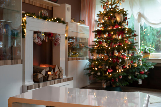Template of festively decorated living room at Christmas. Fireplace and Christmas tree are out of focus. In the foreground is an empty white table on which objects can be added. Copy Space.