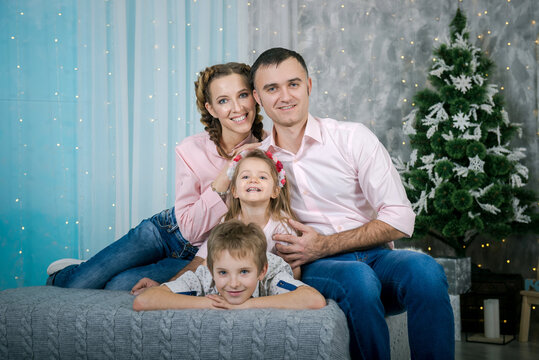 Family in home interior of Christmas and New Year. parents and children are happy together at christmas.  Mom, dad, daughter, son