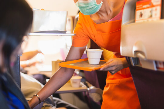 Flight attendant in facial mask protection from covid-19 serves passengers a drink.