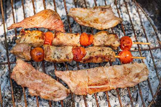 Prepared meat brochettes with vegetables over grill