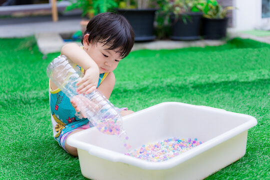 Preschool child boy is using two hands to hold plastic bottle to pour water beads or rainbow beads into white basin. Happy child are sweet smile. Wear blue shirt, yellow border. Toddler 2 years old.