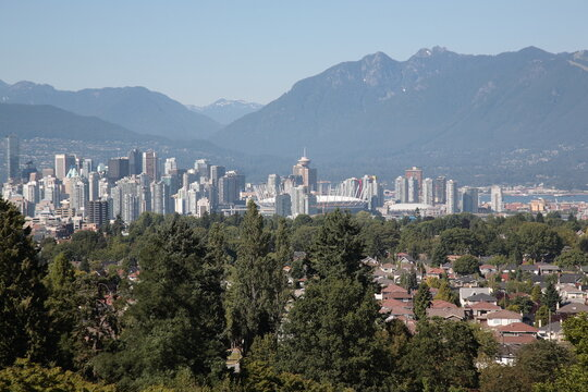 View of Vancouver downtown skyline with mountains and ocean during summer seen from Queen Elizabeth Park in Vancouver,  British Columbia, Canada