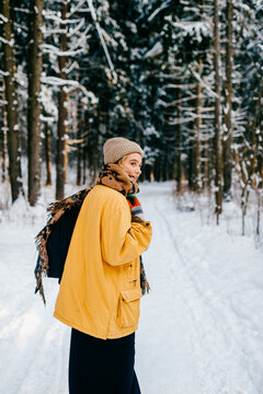 Young stylish hipster girl in yellow jacket with a warm scarf walking in the snow forest