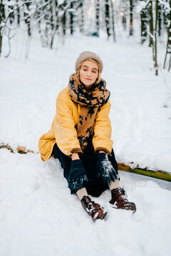 Young stylish hipster girl in yellow jacket sitting on the wood in the snow forest