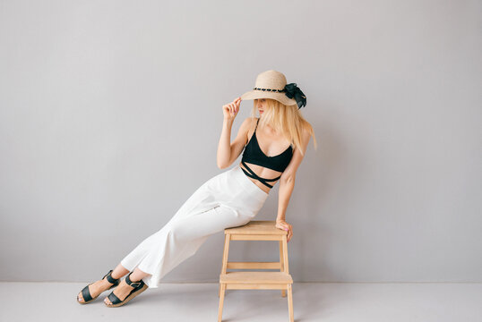 Beautiful young stylish blonde model posing on stepladder in studio