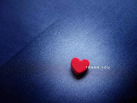 The word Thank You and red heart on glittering dark blue paper background.