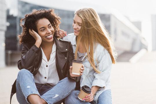 Laughing young women friends talking and having fun in a city. Beautiful joyful young women enjoying life outdoor. Cute girls smiling and hugging. People, lifestyle, friendship, enjoy life, have fun