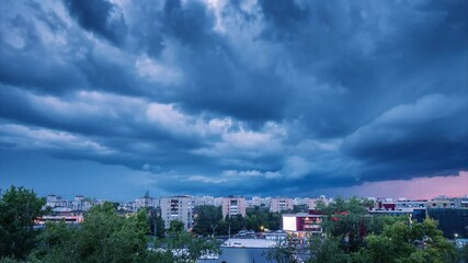 Fotobehang - Dramatic storm clouds moving in dusk sky over cityscape. Timelapse, 4K UHD.