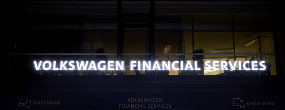 Volkswagen Financial Services illuminated billboard with the name of the financial institution in the pedestrian zone of Wolfsburg, Germany, November 21, 2020.