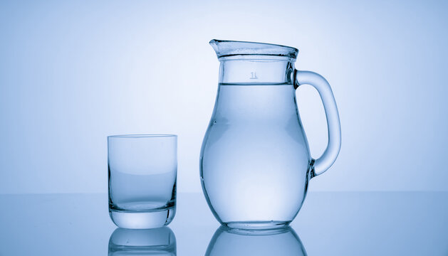 Pitcher with drinking water and a glass with a drink, blue tone