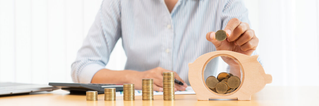 woman hand putting money coin into piggy bank with step of growing stack coins for saving money for future investment concept