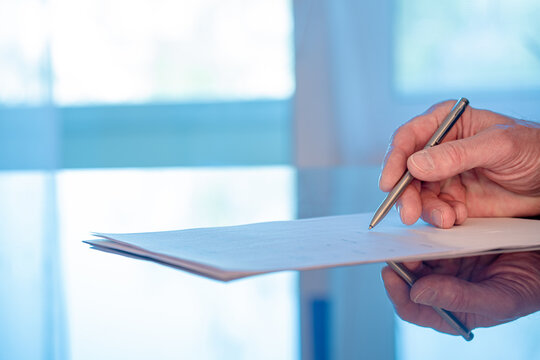 Man signs a document form with a ballpoint pen in the office