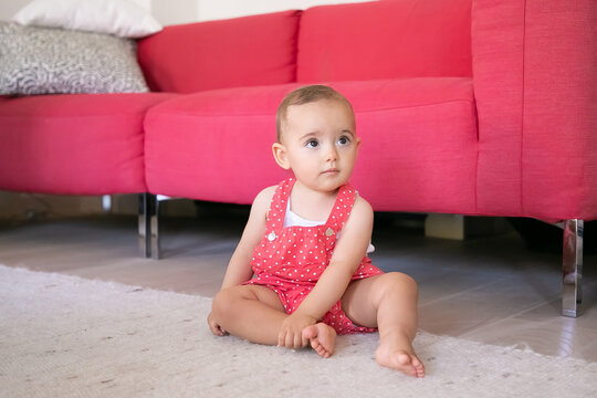 Adorable little baby sitting on carpet barefoot in living room. Funny pensive girl in red dungarees shorts looking at someone and touching her leg. Weekend, childhood and being at home concept