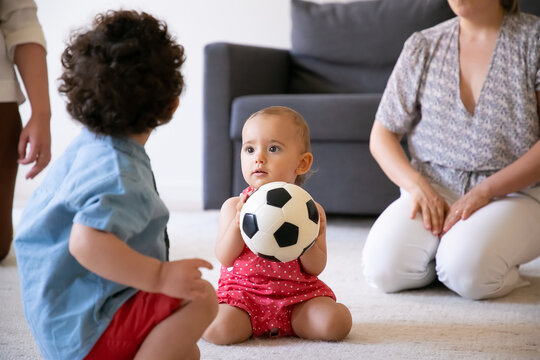 Funny baby girl holding soccer ball, sitting on carpet and playing with brother in room. Cropped mothers having fun with kids. Back view of curly boy. Family indoors, weekend and childhood concept
