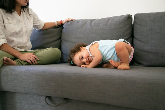 Cute funny baby girl in pale blue dress lying on grey couch near mom. Cropped shot. Parenthood and childhood concept