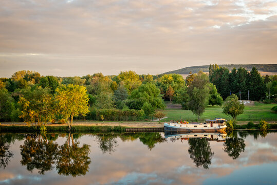 Boat on the Yonne river with reflections at sunset near Joigny in Burgundy, France.