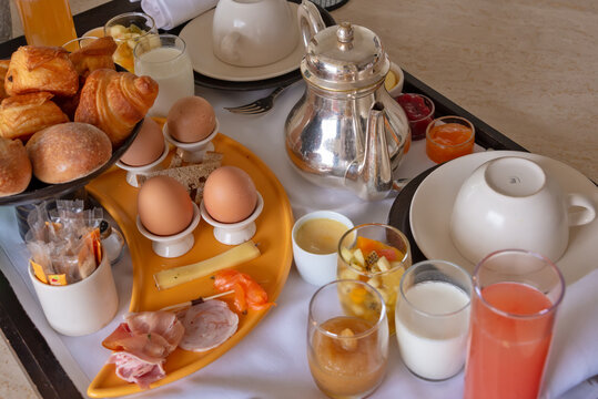 Luxury hotel breakfast with eggs, ham, fruits, croissants and tea on a tray