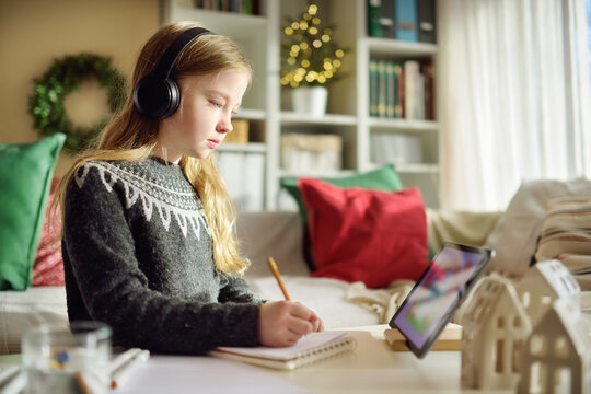 Young schoolgirl doing her homework with digital tablet at Christmas time. Child using gadgets to study. Online education and distance learning. Homeschooling during quarantine.
