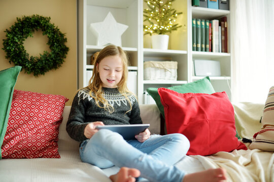 Cute young daughter having online video call on Christmas time. Chatting with distant family during pandemic. Staying safe during winter holidays.