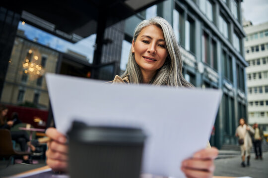 Joyful businesswoman working with documents in outdoor cafe