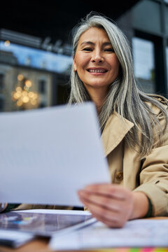 Cheerful woman working with documents in outdoor cafe