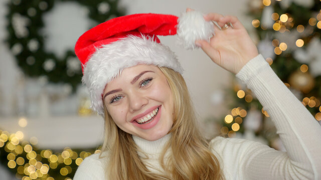 Young blond beautiful smiling woman in sweater and Santa hat on christmas tree background