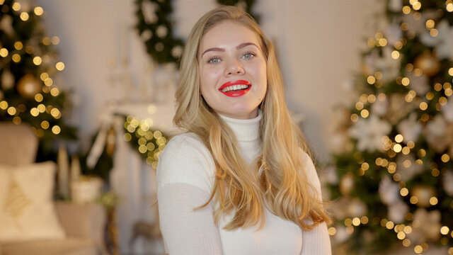 Fashionable smiling woman wearing knitwear cozy sweater in front of christmas tree