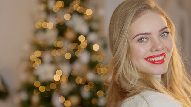 Portrait of smiling, blond, girl with long hair in a cozy sweater on the Christmas tree background