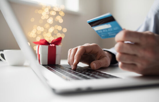 Shopping online during holidays. Man using laptop computer and credit card ordering Christmas gifts. Shopping, internet banking, store online, payment, surprise, spending money, holiday concept