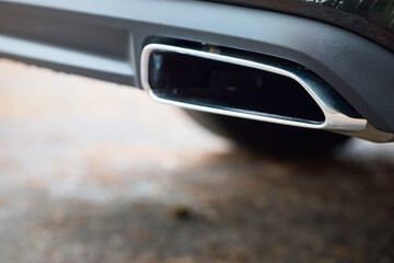 Chrome exhaust pipe of powerful luxury car selective focus with black bodywork as part of exhaust system car muffler of modern new car with out of focus background with copyspace.