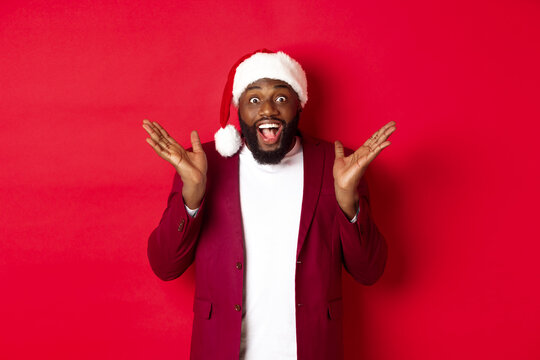 Christmas, party and holidays concept. Surprised and happy african american man in santa hat, looking with rejoice at camera, standing against red background