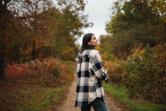Beautiful brunette nice woman strolling in autumn forest