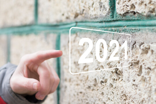 Businessman presses button 2021 new year on virtual panel, against the background of the stone.
