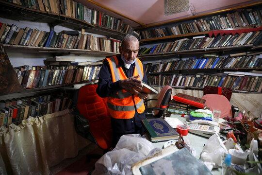 Mohammad Salem Abu Zakrya fixes an abandoned copy of the Koran at his library in Jerash