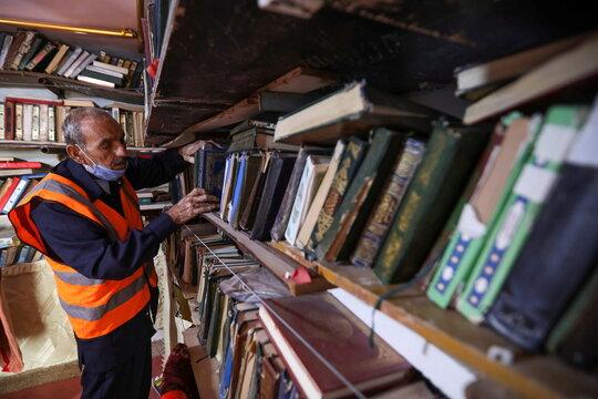 Mohammad Salem Abu Zakrya arranges books at his library in Jerash